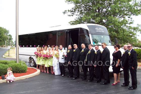 Bridesmaids and Groomsmen With A Wedding Couple In Front Of A Party Bus